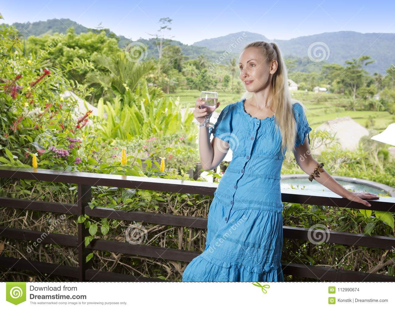 Young beautiful woman in a long dress with a glass of wine looks at the tropical nature