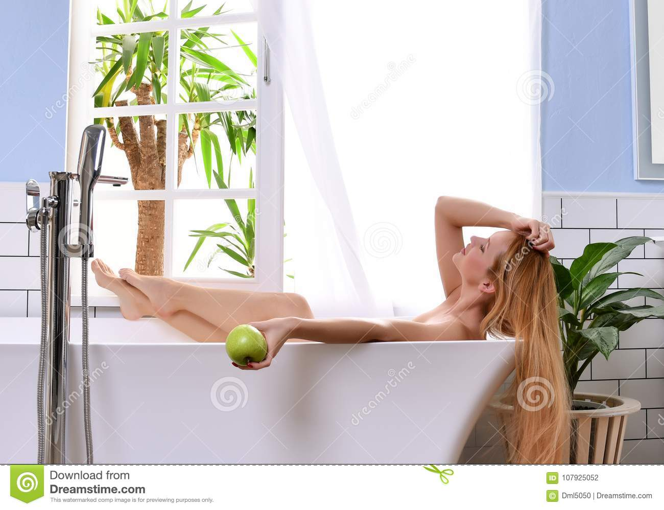 Young beautiful woman lying in bathtub and taking bath near open bathroom window