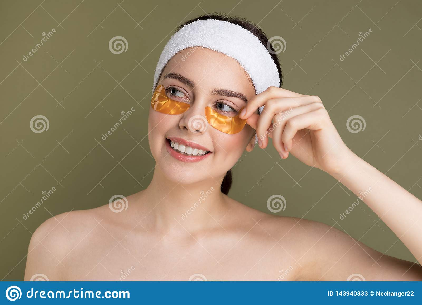 Young beautiful woman with natural make up removing gold patch from under her eye