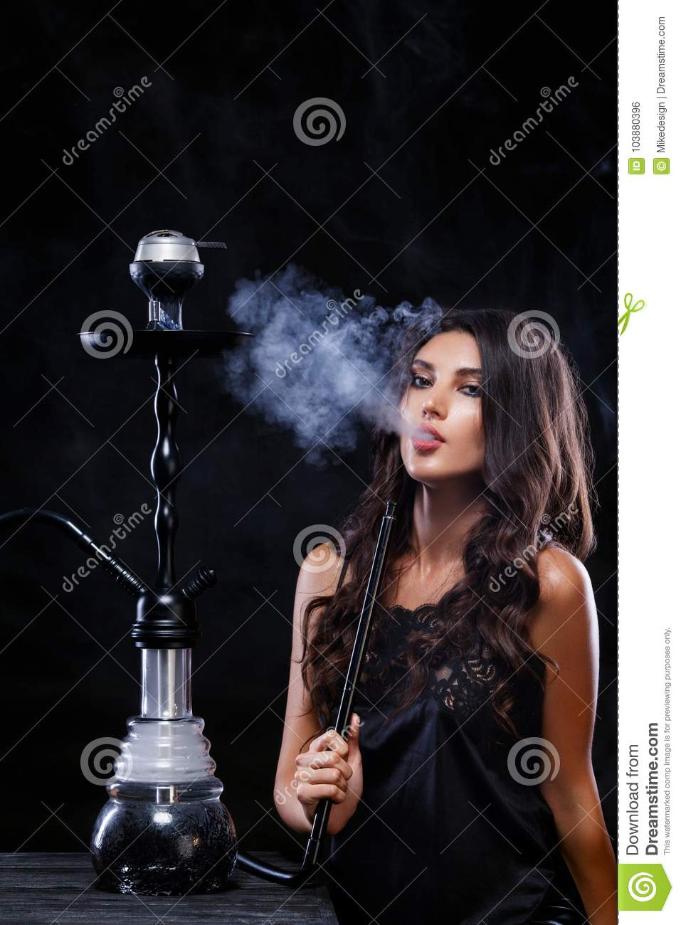 Young, beautiful girl in trendy club clothes and perfect make up smoke a  hookah. The pleasure of smoking. smoke
