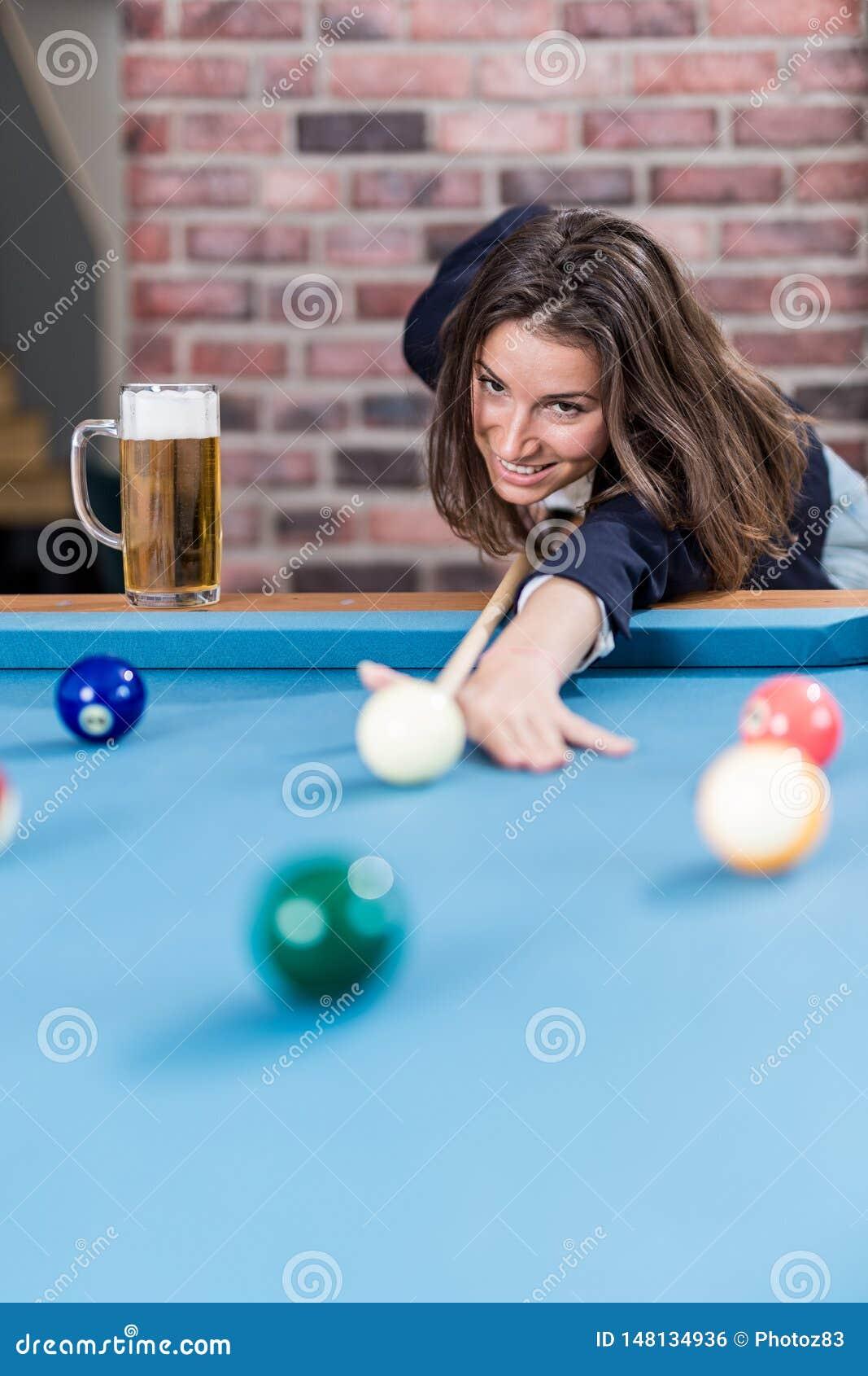 Young beautiful woman playing billiards