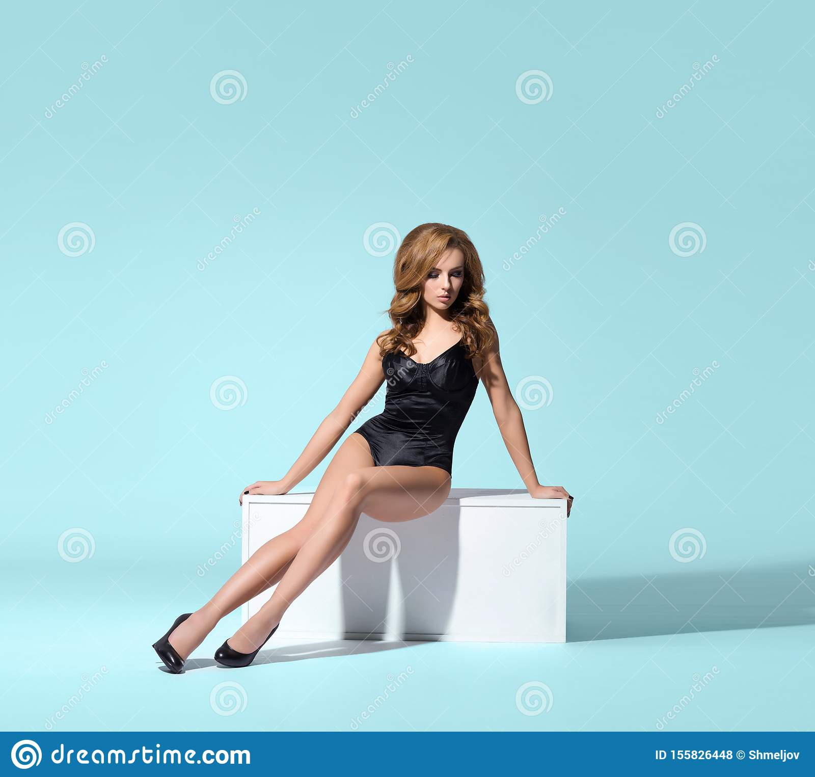 Young beautiful woman posing in lingerie over colored background in studio. Girl in underwear.
