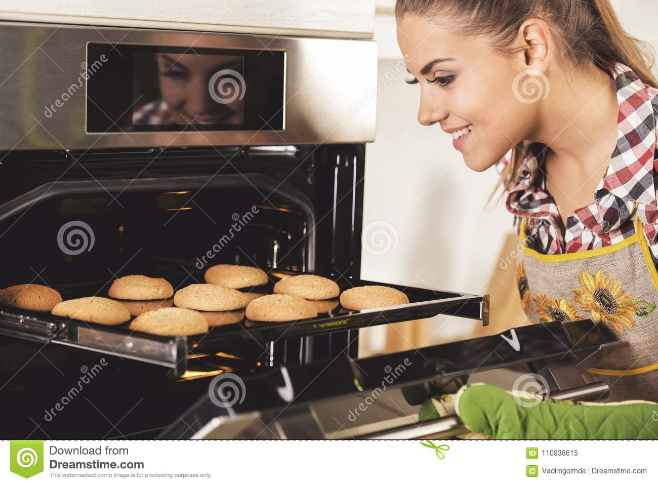 Young beautiful woman pulls cookies from the oven