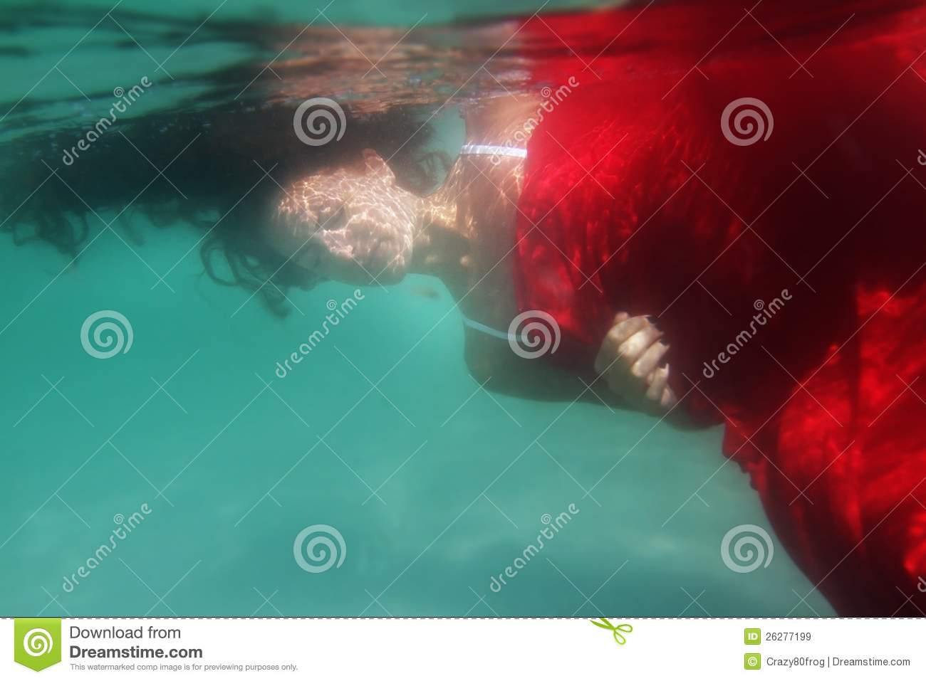 Young beautiful woman in red dress underwater