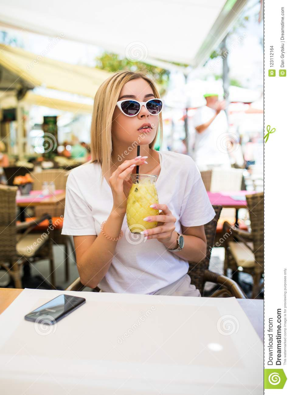 Young beautiful woman in round sunglasses with cocktail at the terrace of cafe having fun