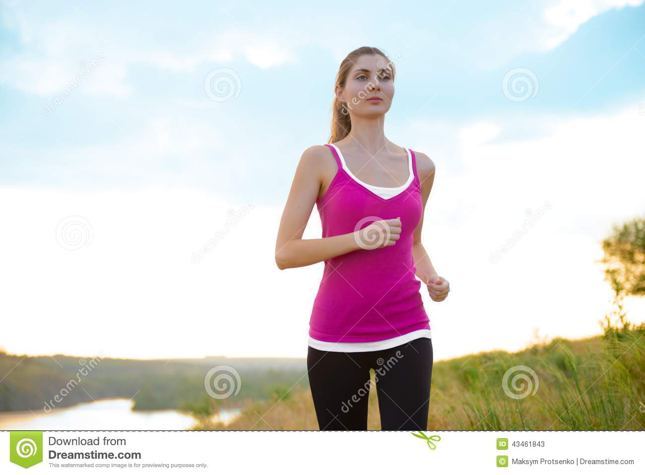 young beautiful woman running on the mountain trail in the