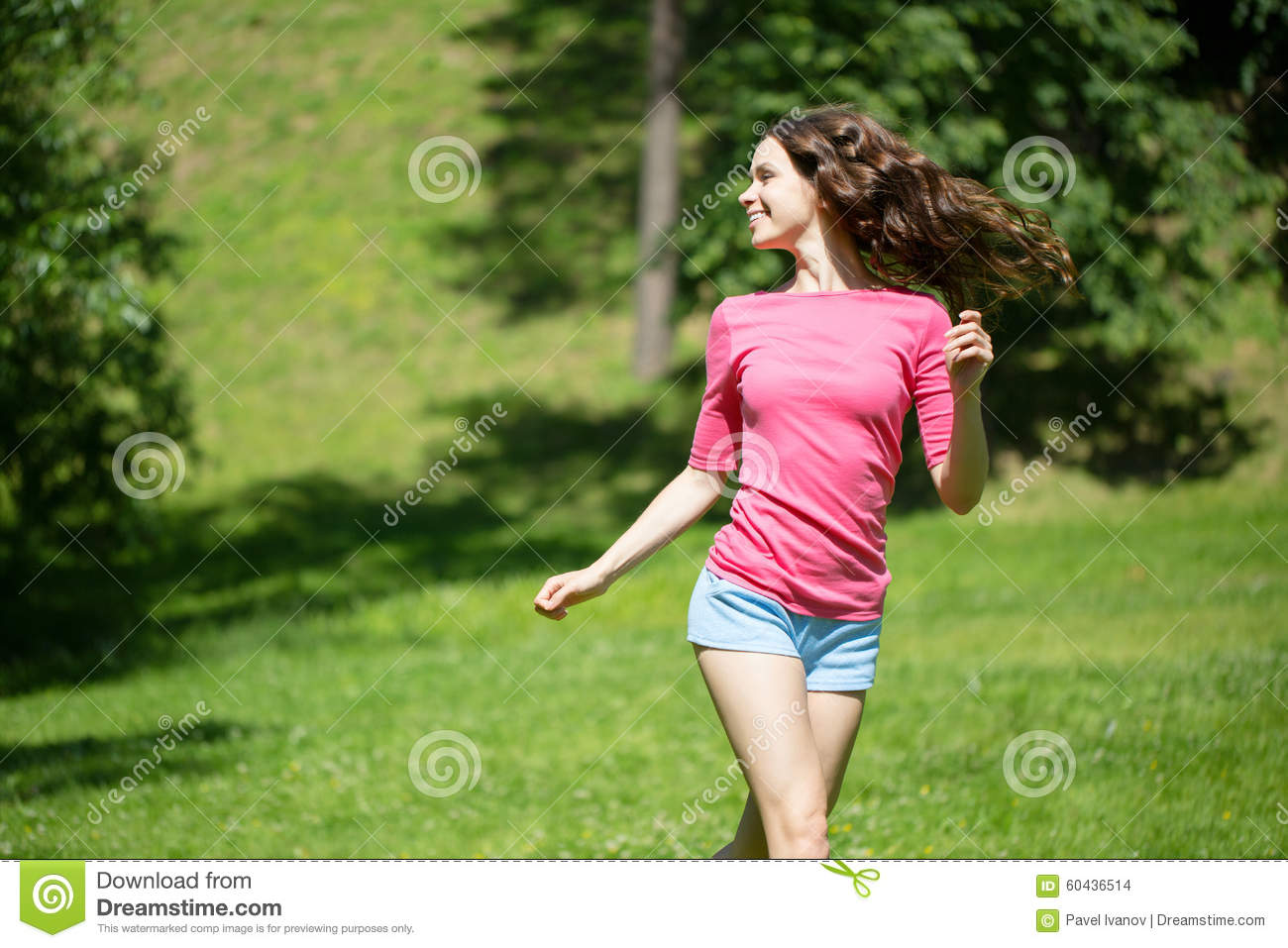 young beautiful woman running in the park stock photo