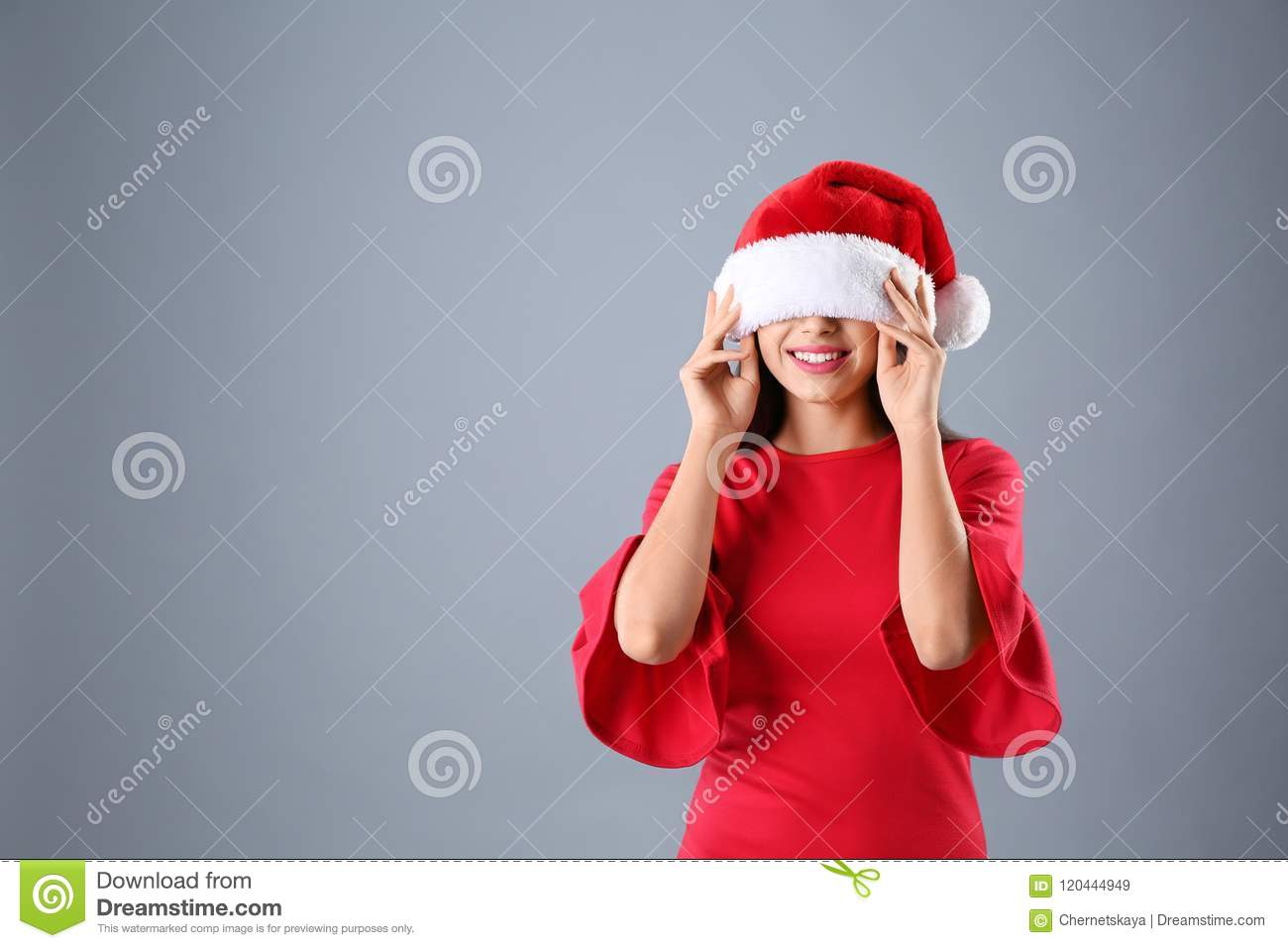 Young woman in Santa hat on grey background. Christmas celebration