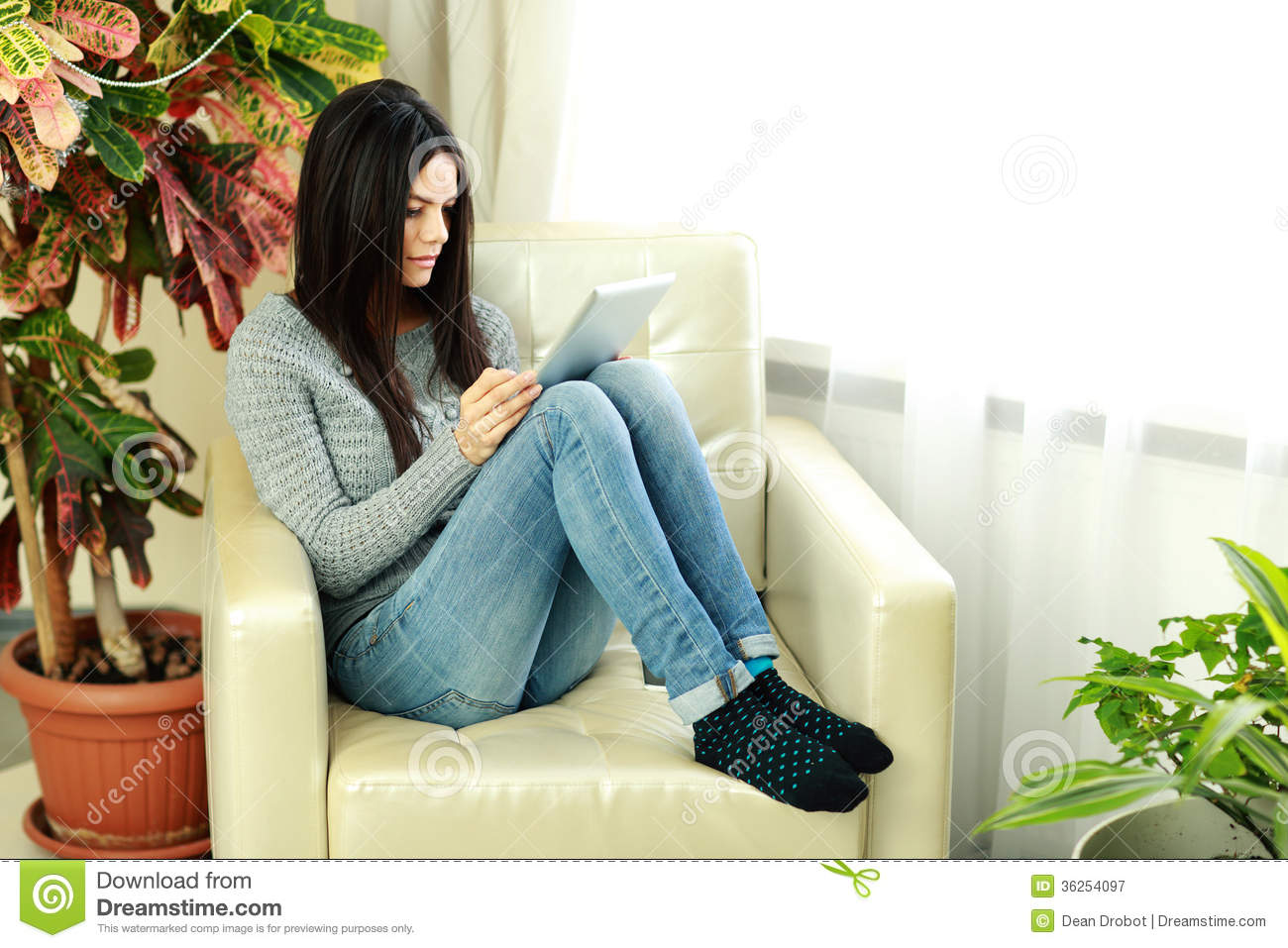 Young beautiful woman sitting on the armchair with tablet for Sitting in armchair