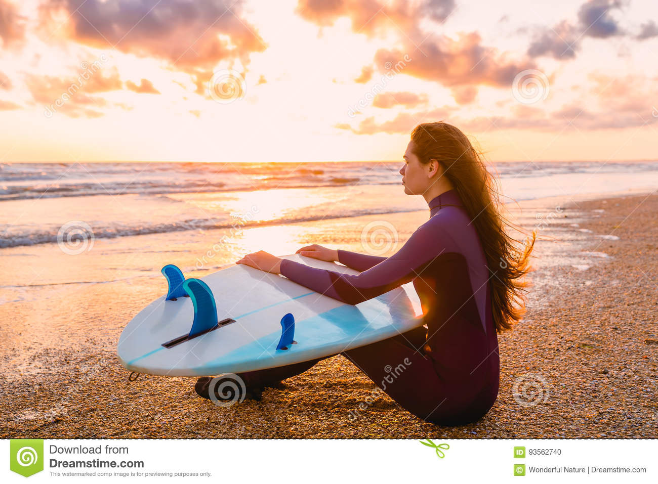Young beautiful woman is sitting on the beach. Surf girl with surfboard on beach at sunset or sunrise. Surfer and ocean