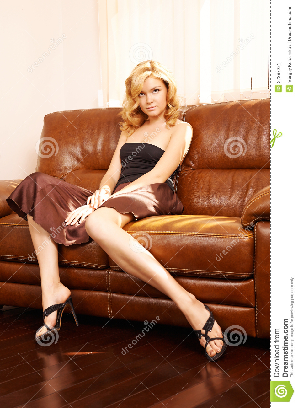 Young Beautiful Woman Sitting On Couch Stock Image
