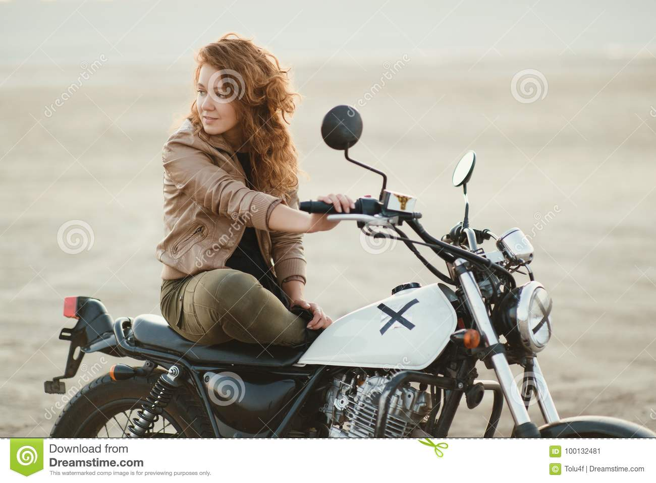 young beautiful woman sitting on her old cafe racer motorcycle in desert at sunset or sunrise