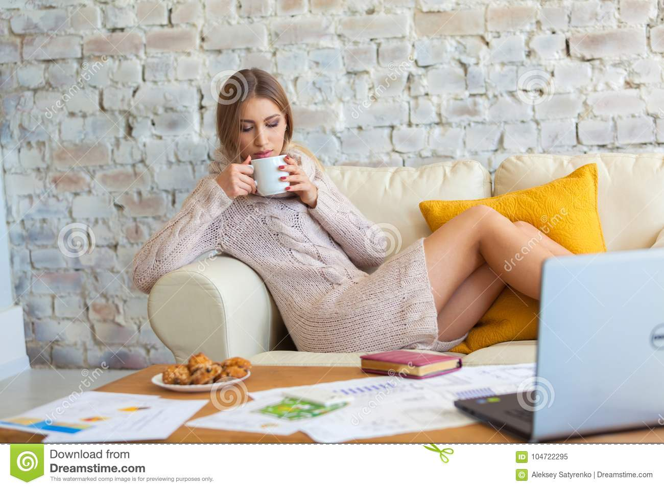Young beautiful woman is sitting on a sofa on a white brick wall background with a cup of coffee. Laptop, documents
