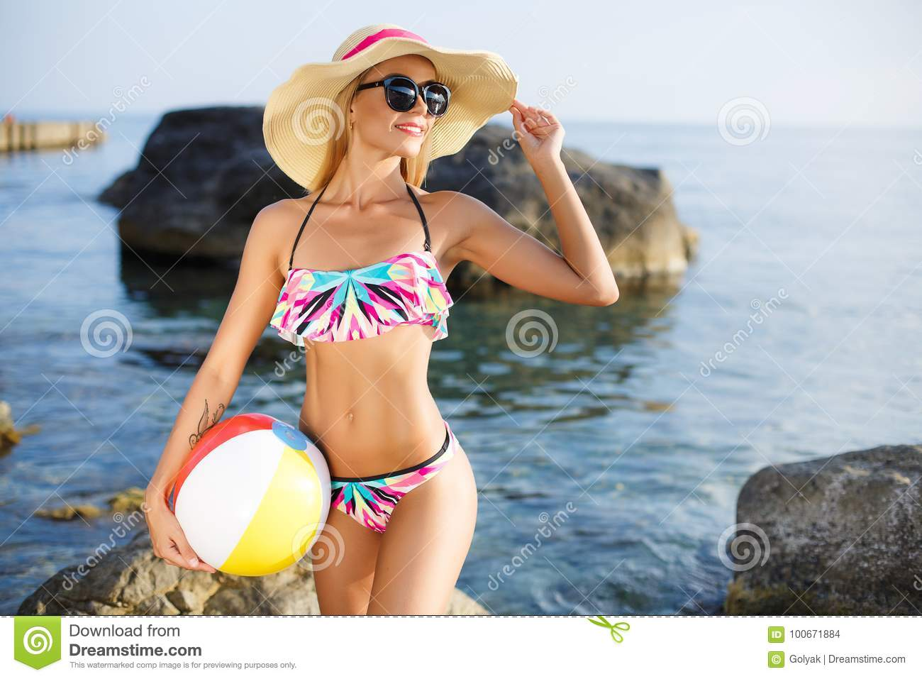 Beautiful slim woman in big hat on the beach