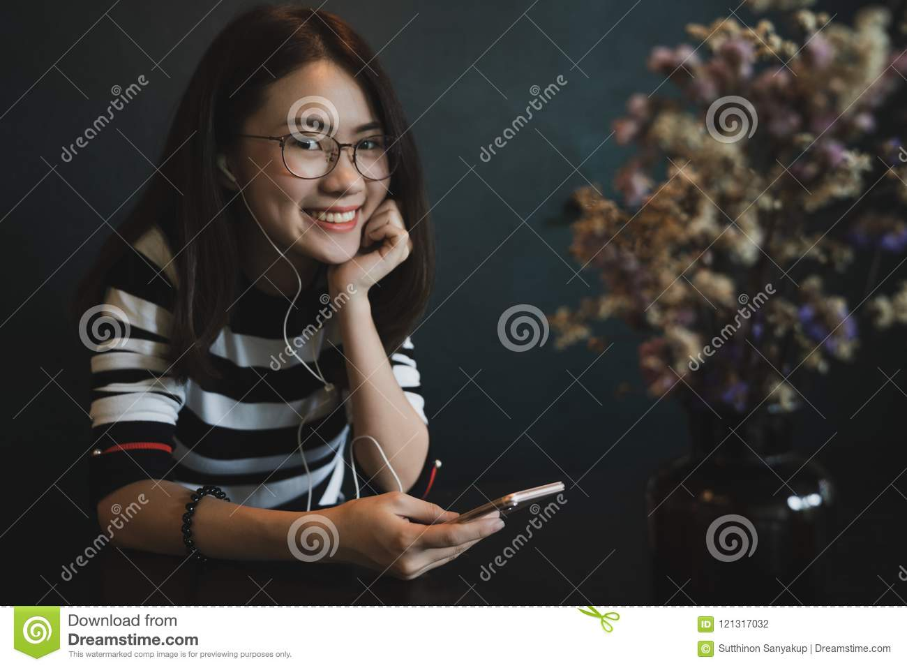 Young beautiful woman with smart phone, Cheerful young woman using smartphone with headphones over black background