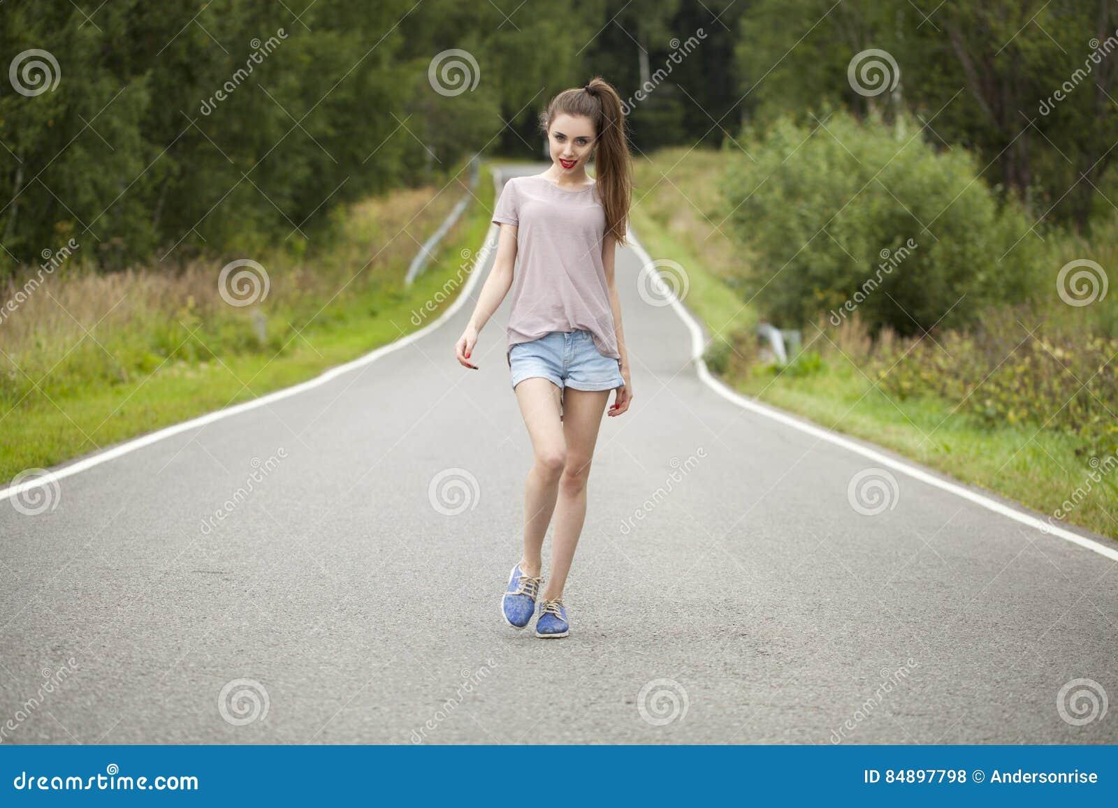 Young beautiful woman walking in a field, summer outdoors