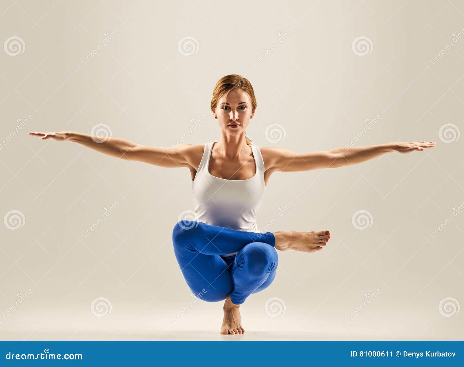 young beautiful yoga pose balancing on one leg stock