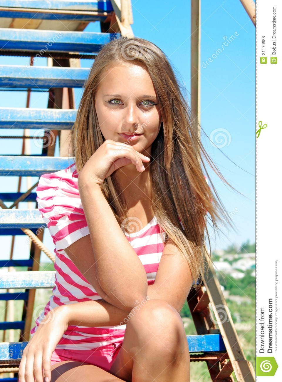 Young Smiling Beauty Sits On A Ladder Over Sky