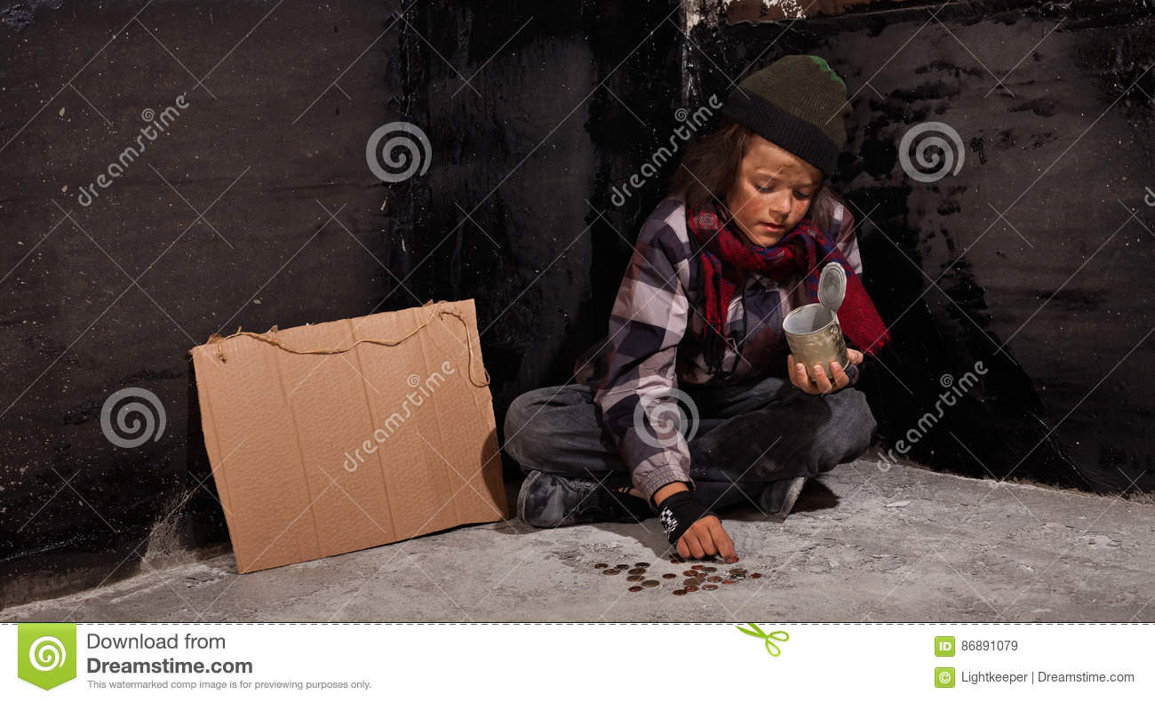 Young beggar boy counting coins - sitting on the ground