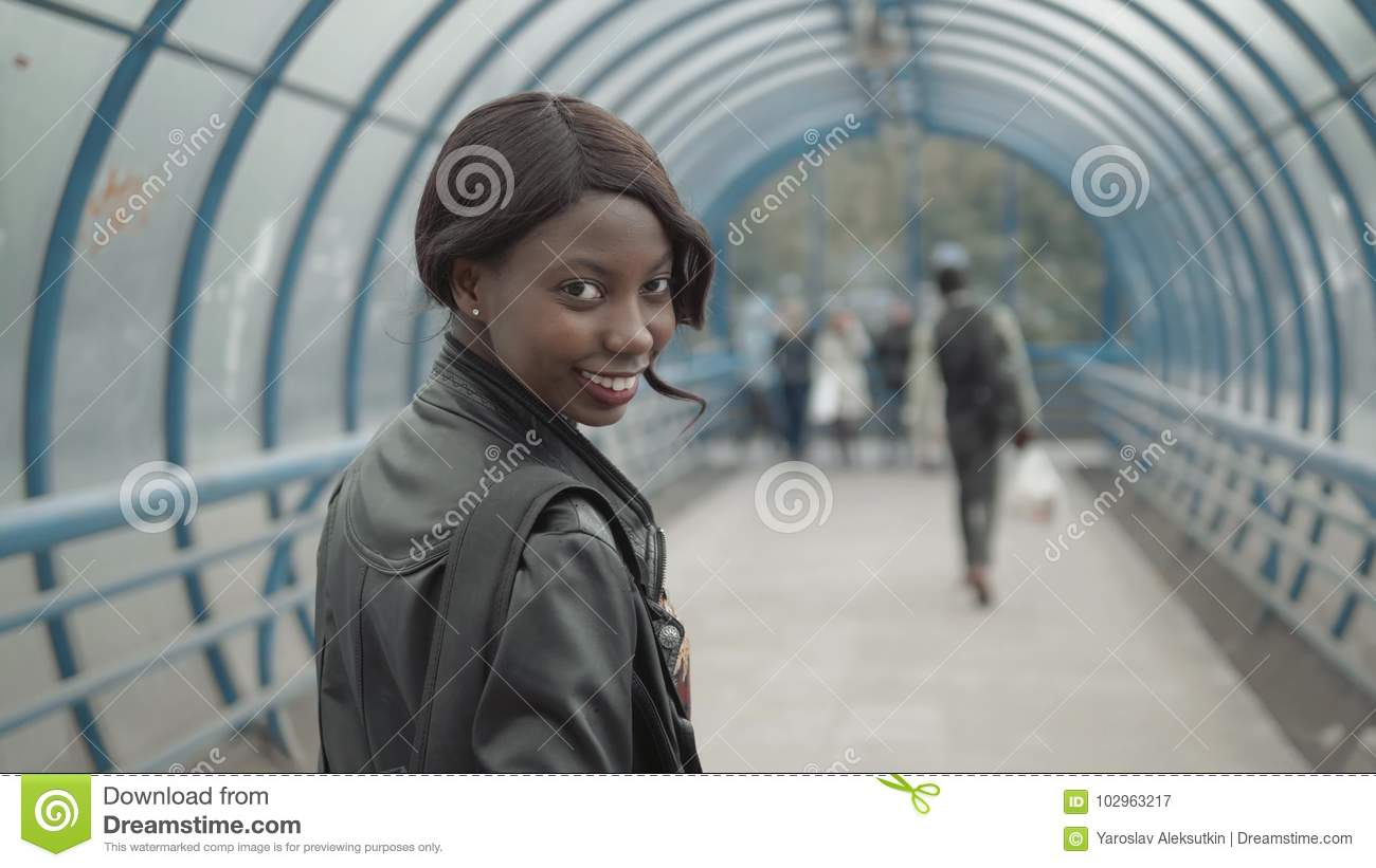 Young black female teacher with afro hairstyle wearing small leather jacket briefcase, walking out from office building