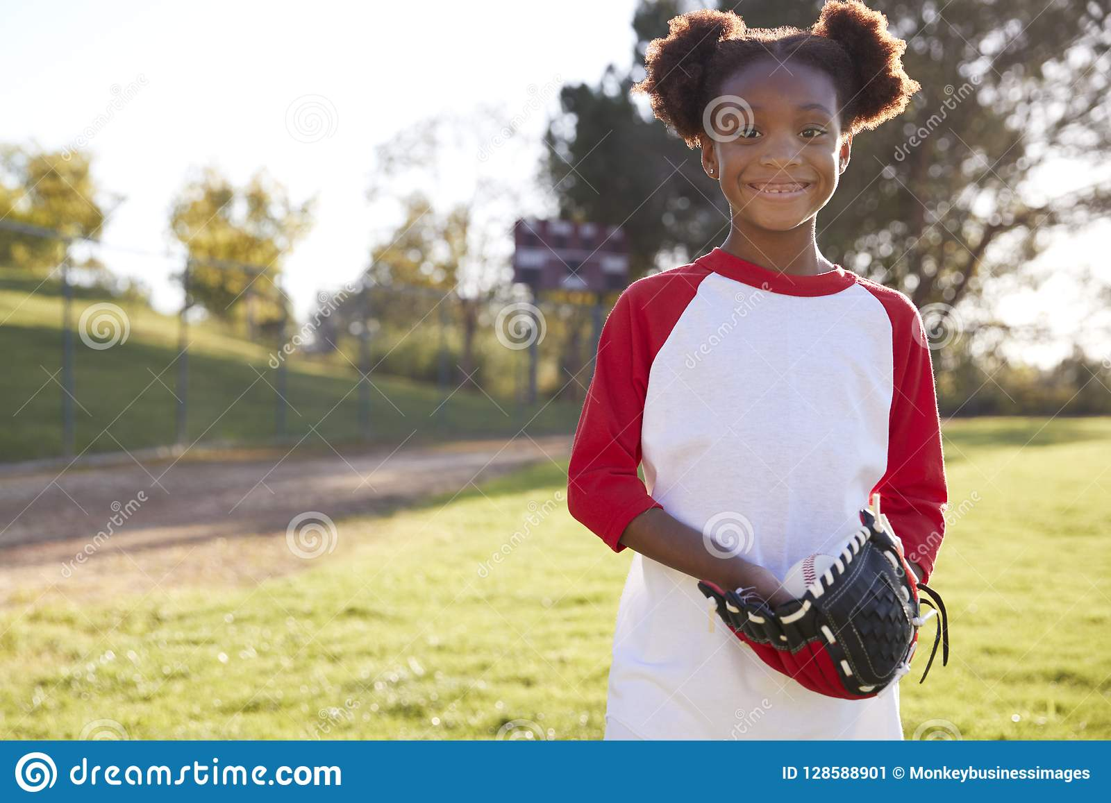 Young Black girl holding baseball mitt smiling to camera
