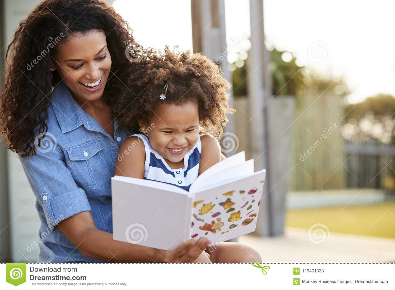 Young black girl reading book sitting on mum�s knee outdoors