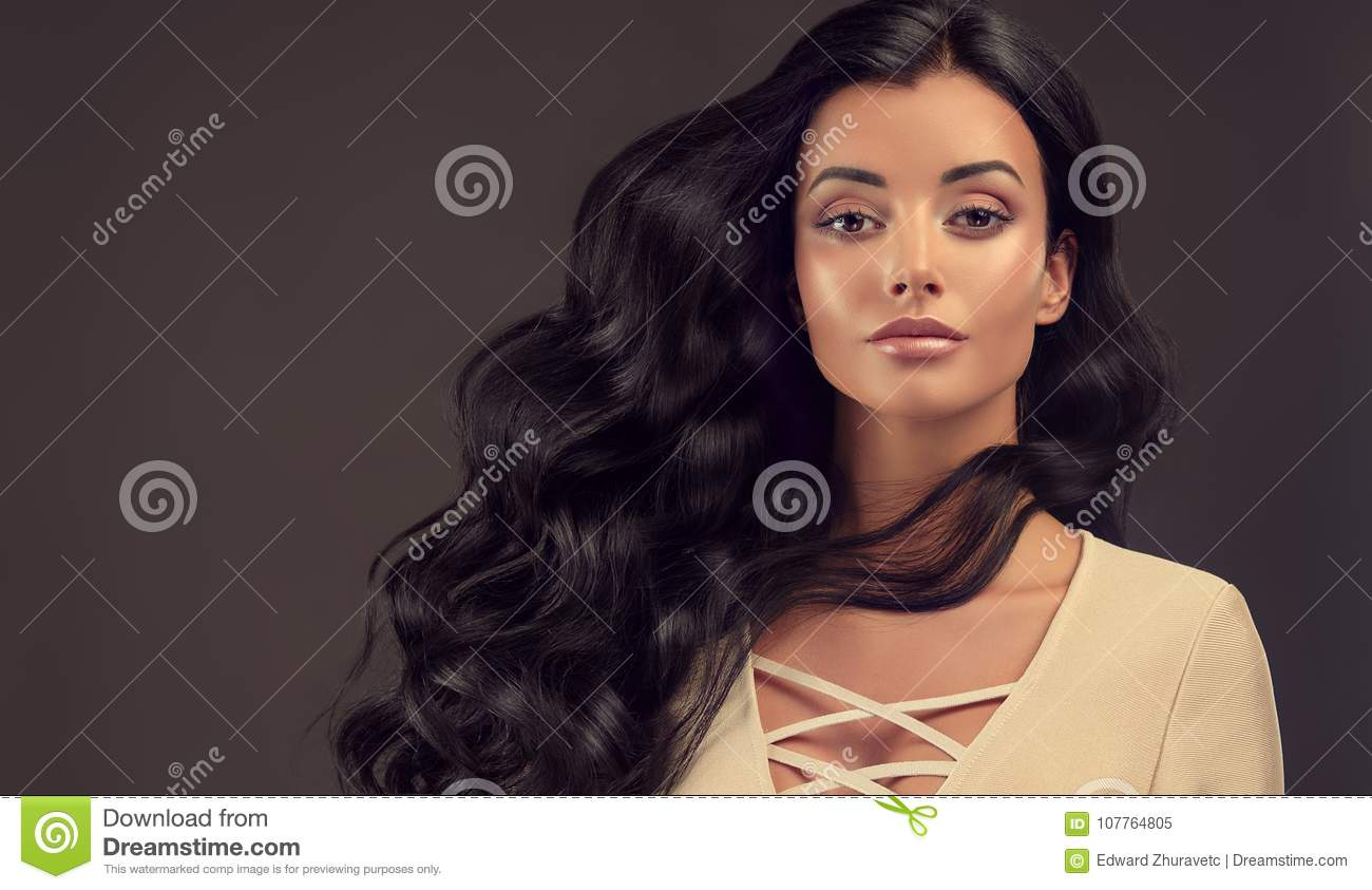 Young black haired woman with voluminous, shiny and wavy hair