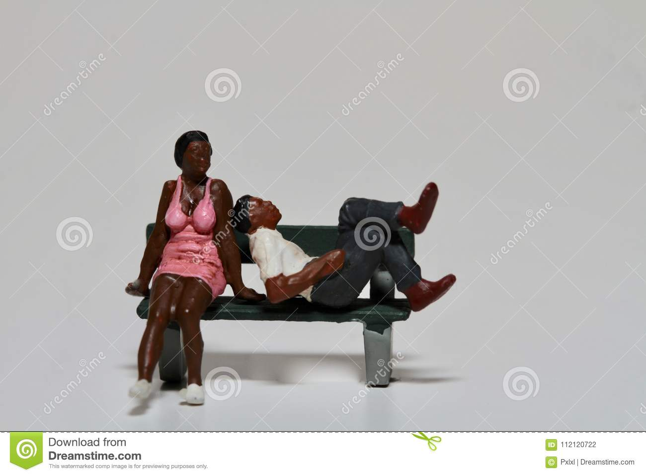 Young black lovers figurines in miniature sitting on a bench