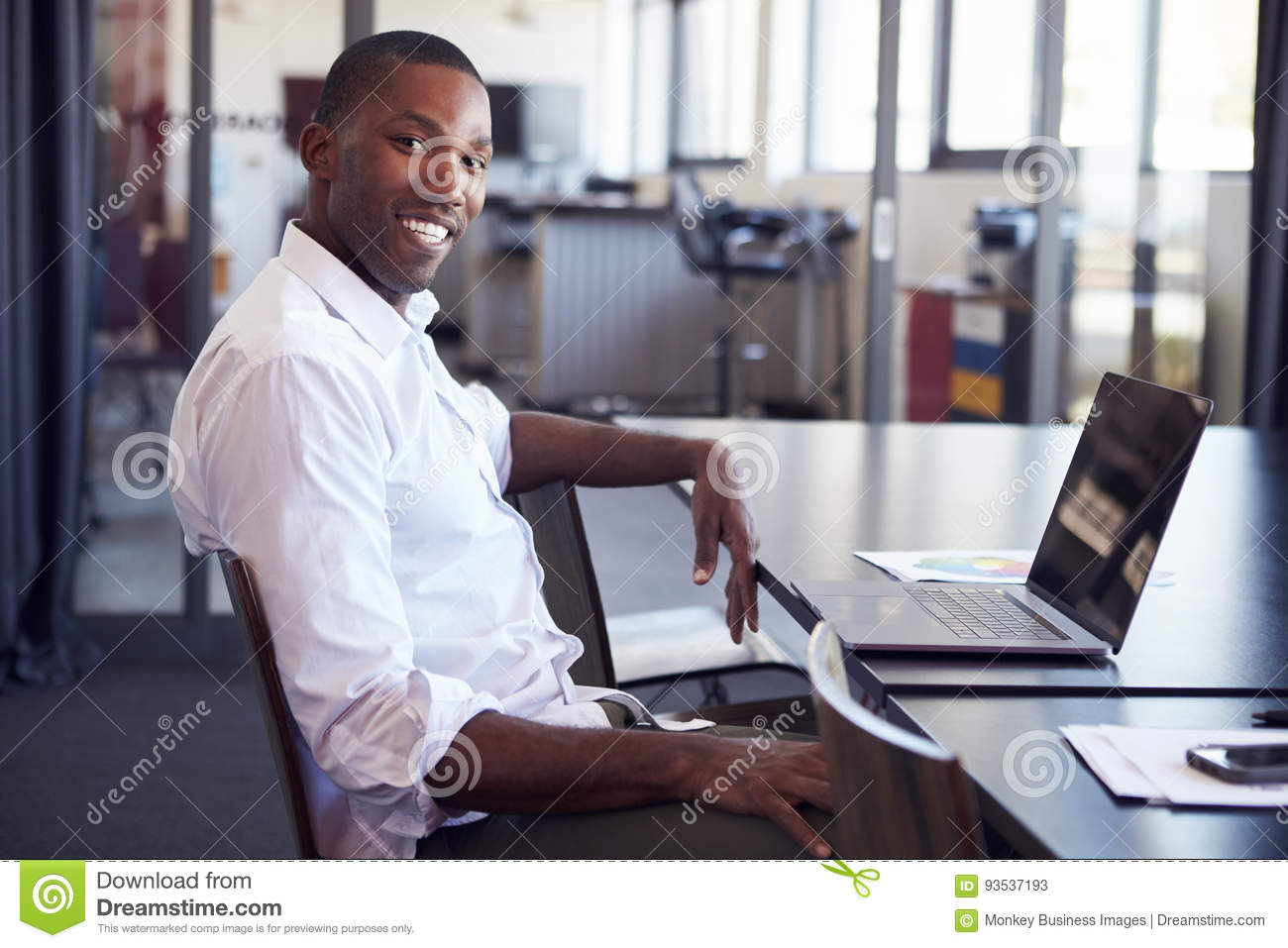 Young black man sitting at desk in office smiling to camera