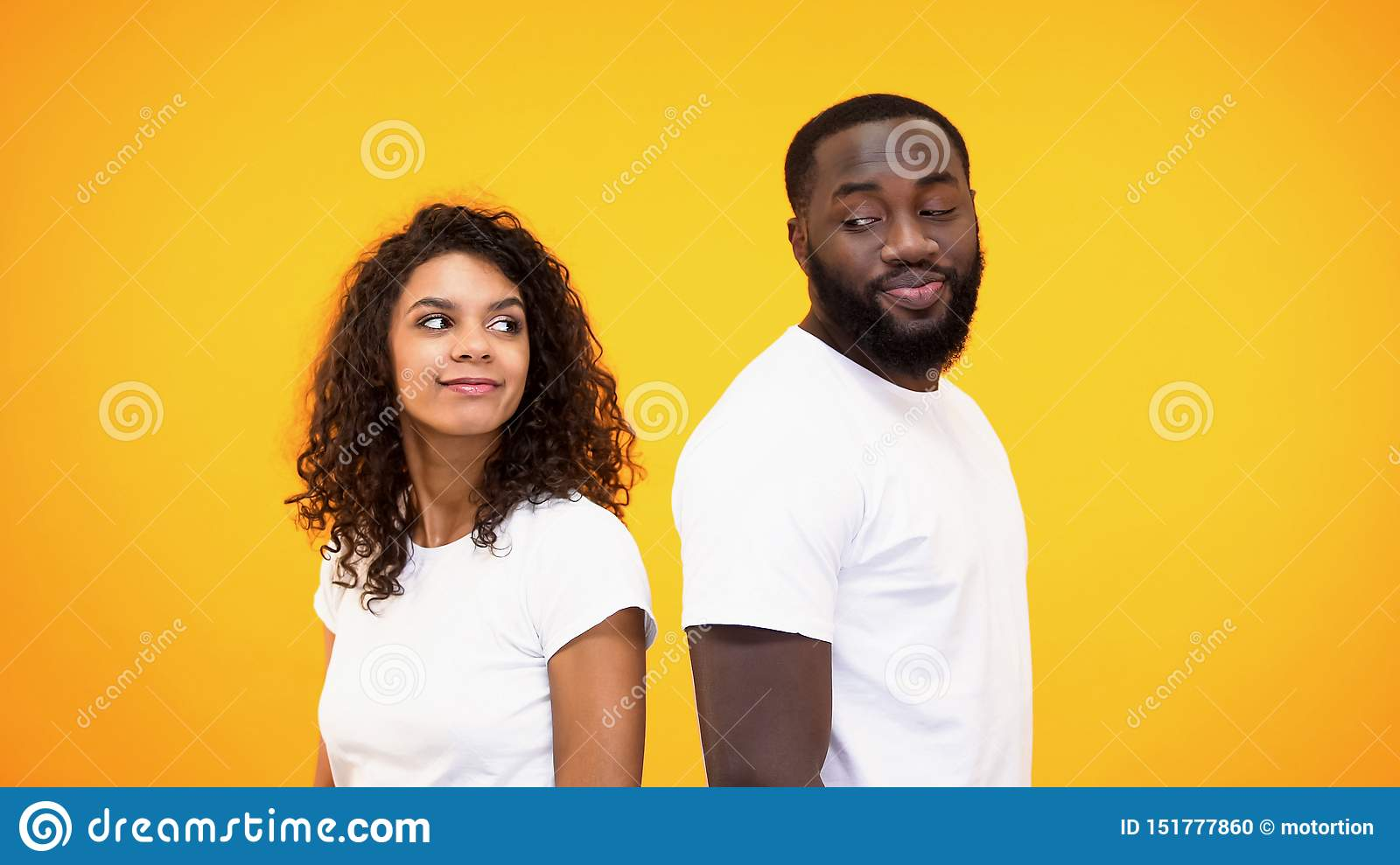 Young Black Man And Woman Looking Each Other Standing Back To Back