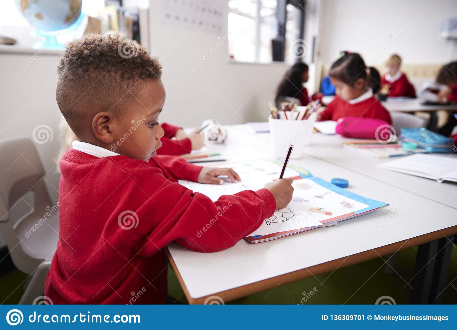 Young black schoolboy wearing school uniform sitting at a desk in an infant school classroom drawing, close up, side view