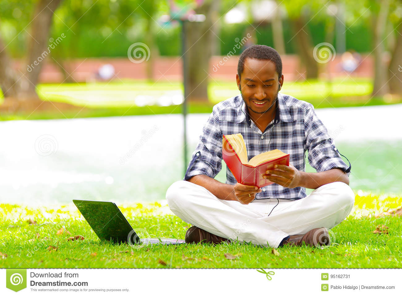 Young Black Tourist Man Sitting Down On Green Grass Reading A Book With His Computer Near To Him In The City Of Quito Stock Image - Image of healthy, flexible: 95162731