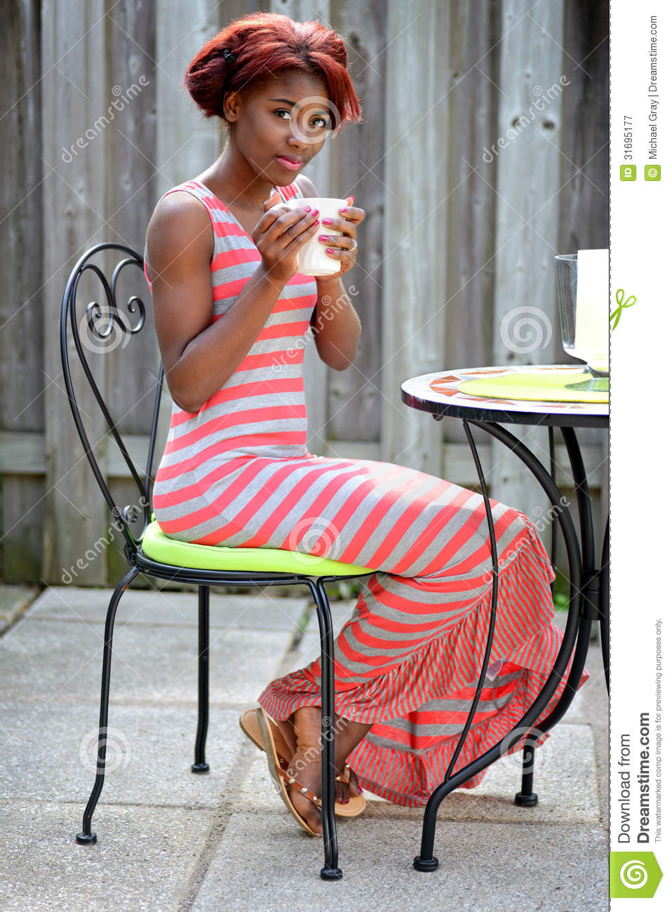 Young Black Woman Enjoying Coffee On The Patio Royalty