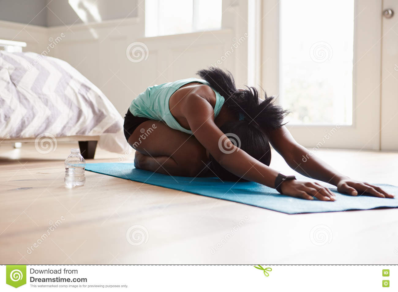 Young black woman practicing yoga in the cat stretch pose