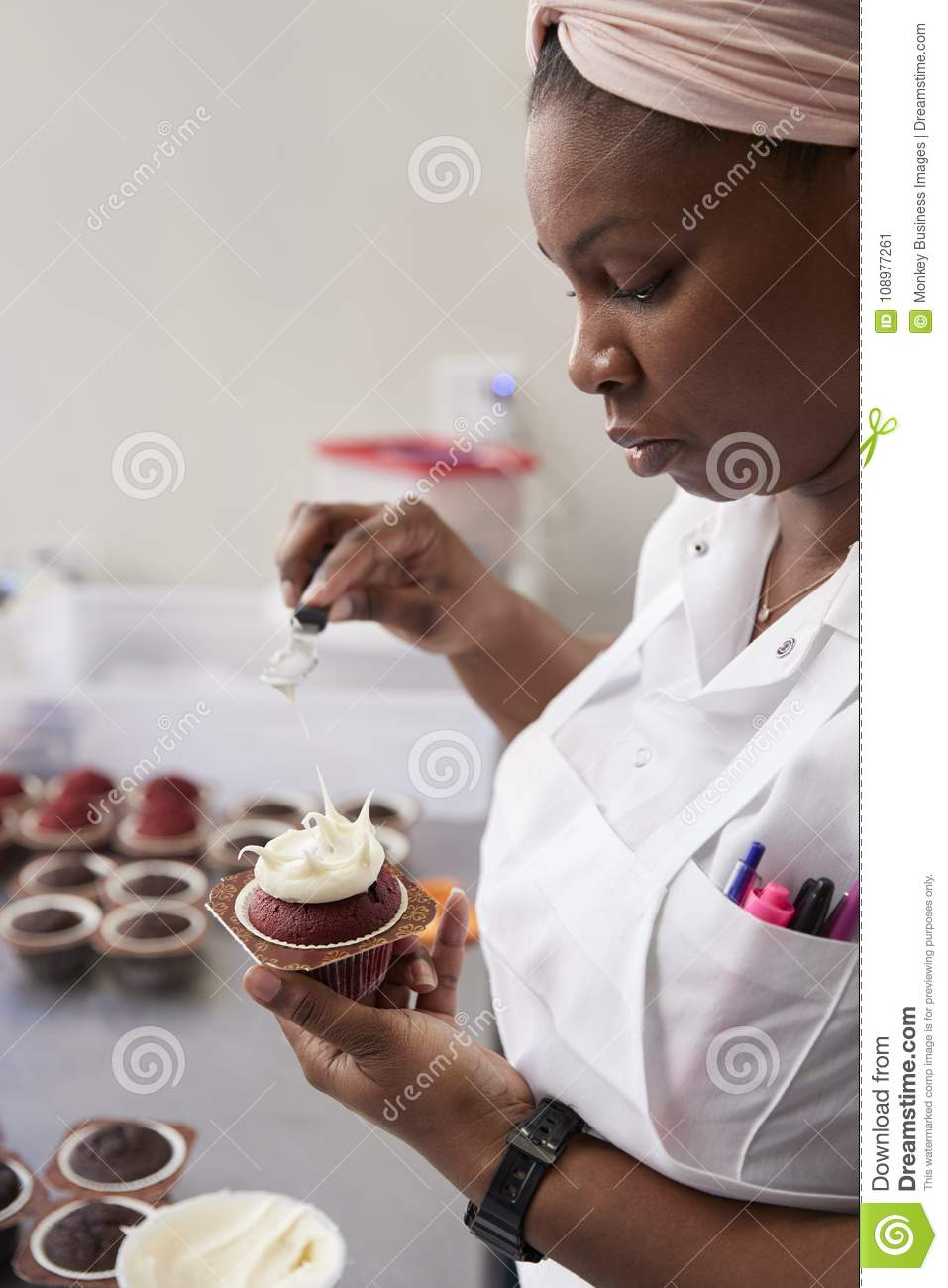 Young black woman preparing food in a bakery, close up