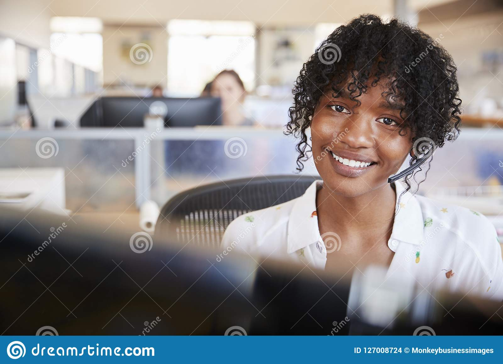 Young black woman working in a call centre smiling to camera
