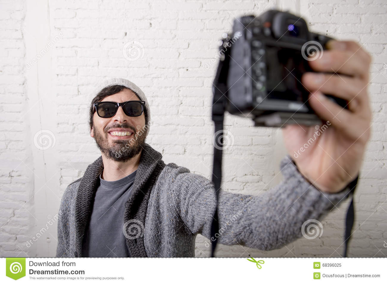 Young blogger man hipster style holding photo camera shooting selfie video and photo