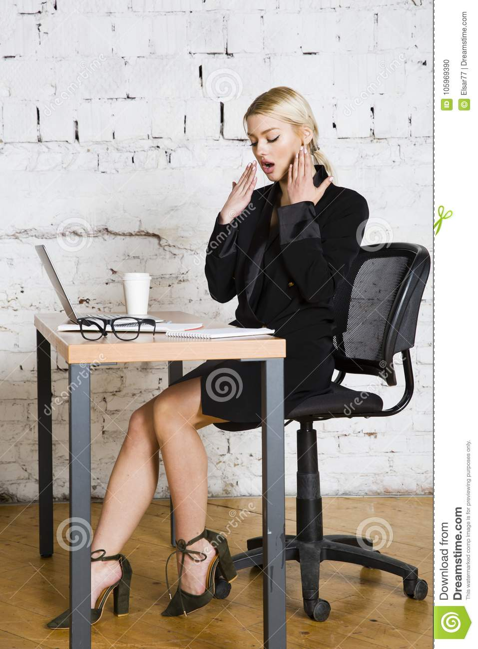 Young blond beauty businesswoman sitting at a office table with laptop, notebook and glasses in suit. Business concept.