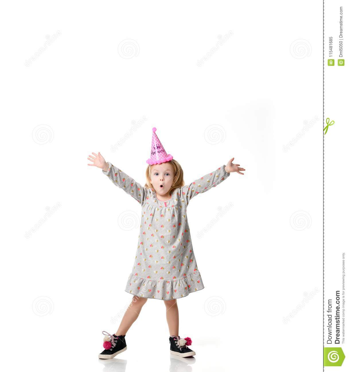 Young blond girl in birthday party princess hat surprised emotions with hands spread up isolated on a white