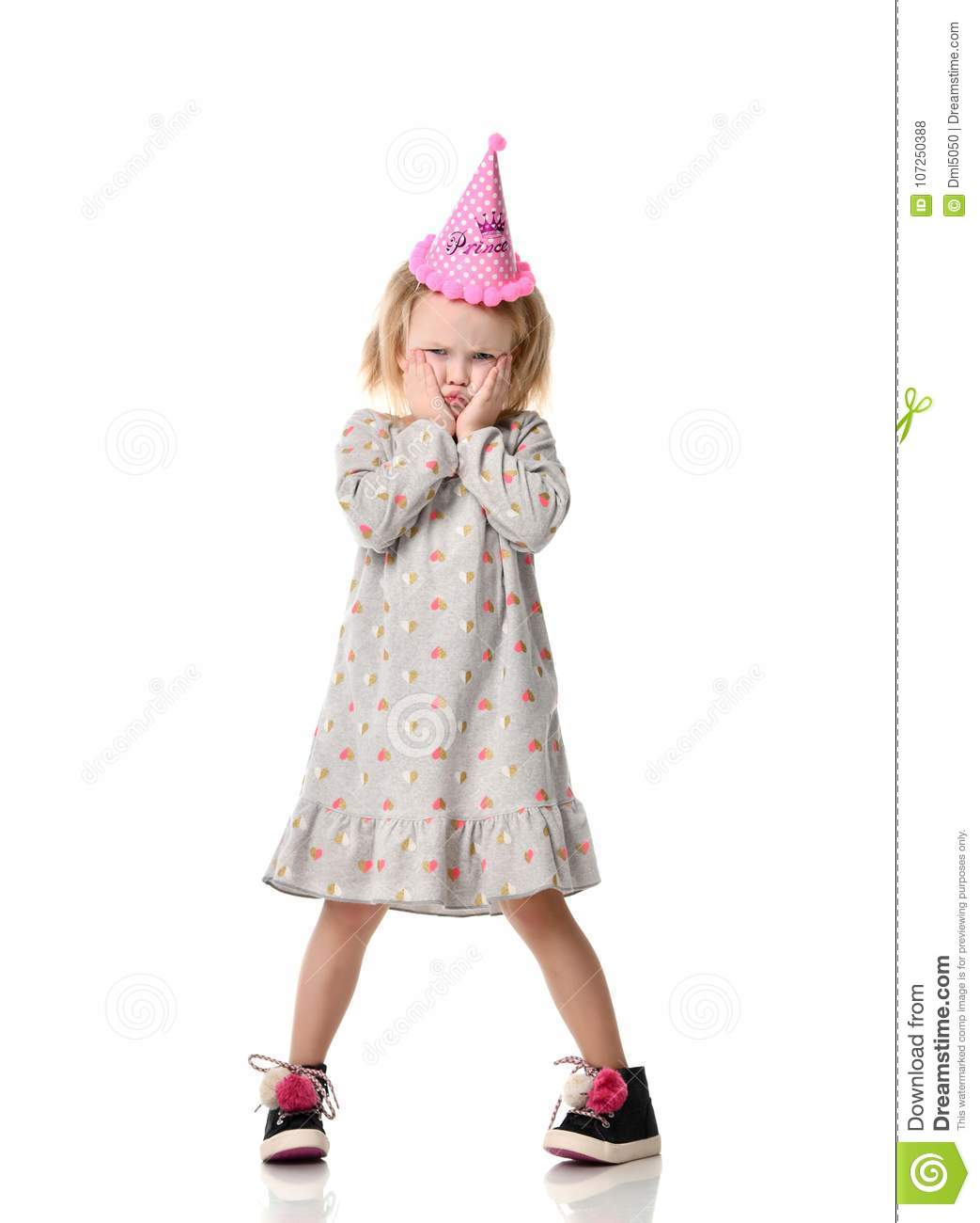 Young blond girl in birthday party princess hat upset sad emotions