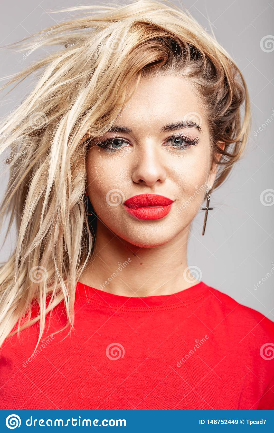 Young blond girl with a red lipstick short in a red t-shirt poses staying against a wall in the studio