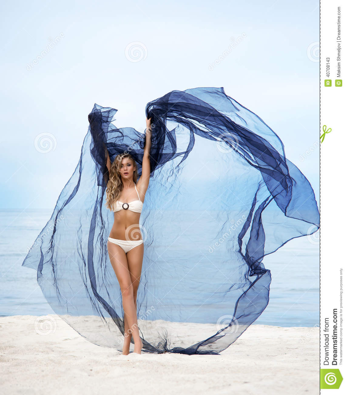 Young blond woman with blue silk posing on the beach