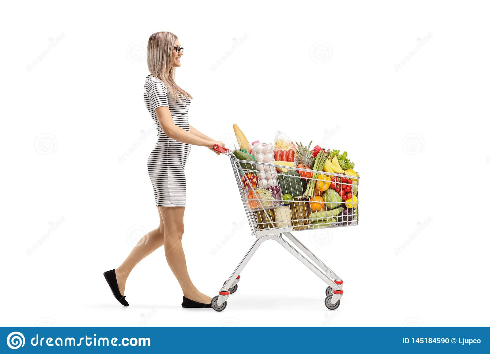 Young blond woman pushing a shopping cart with food products and walking