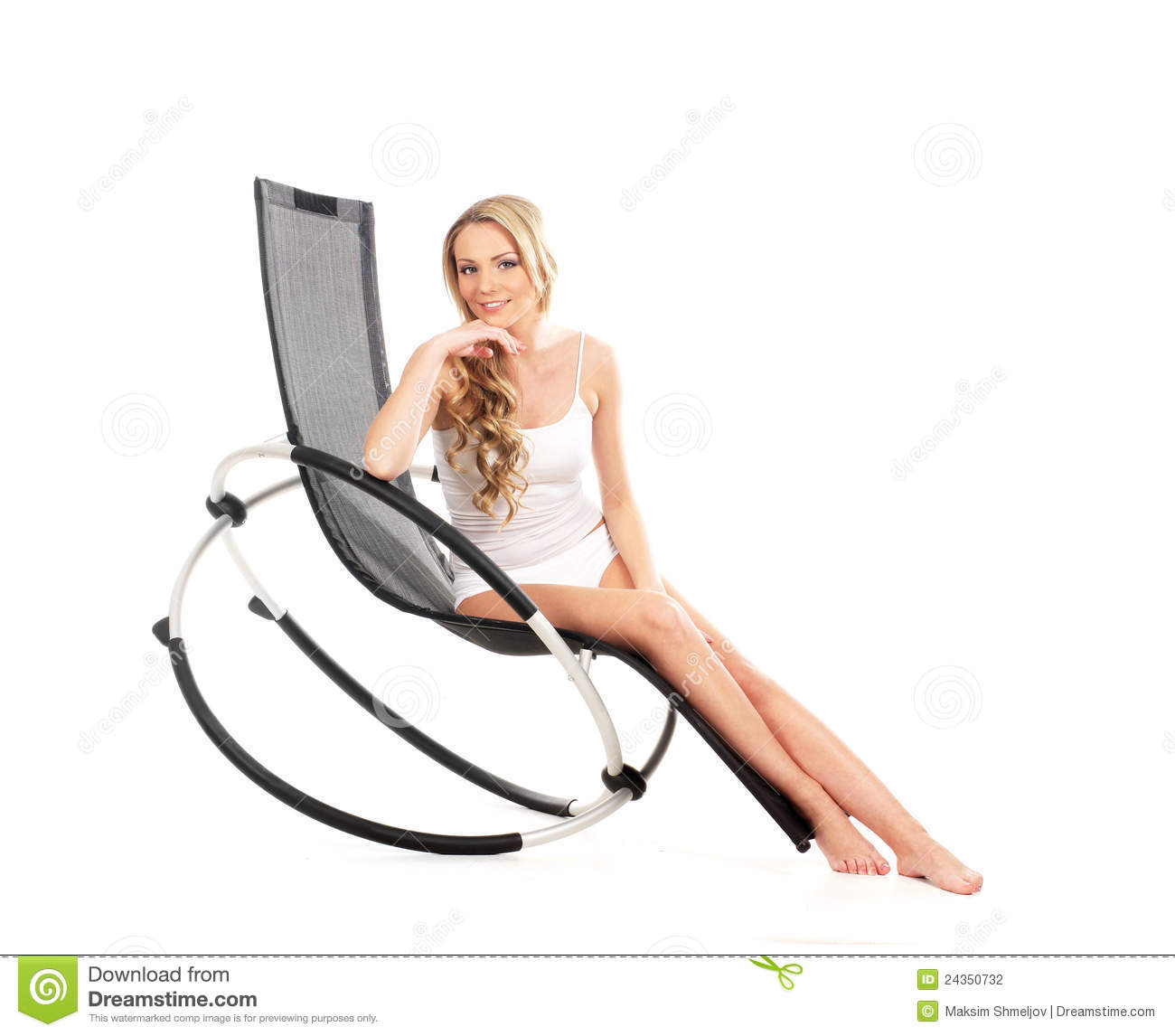 A young blond woman sitting in an armchair stock for Sitting in armchair