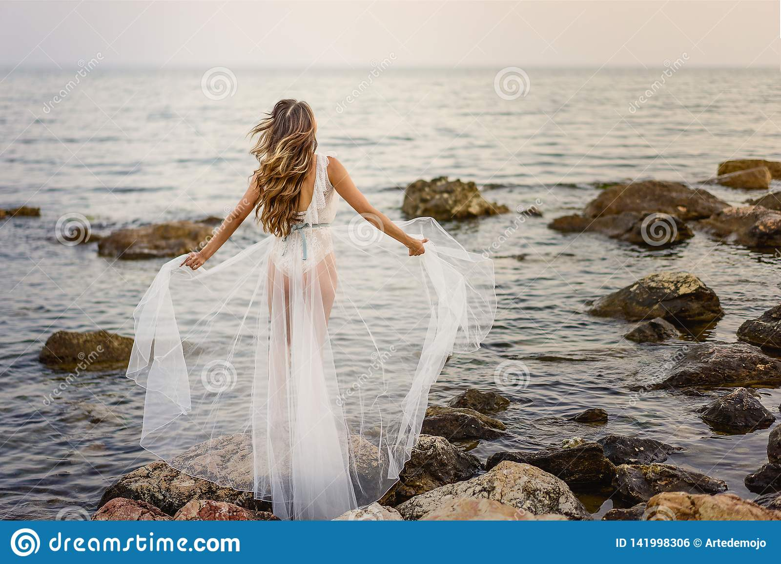 Young blond woman in white summer dress standing on the rocks and looking at the sea. Caucasian girl enjoys beautiful view at sunr