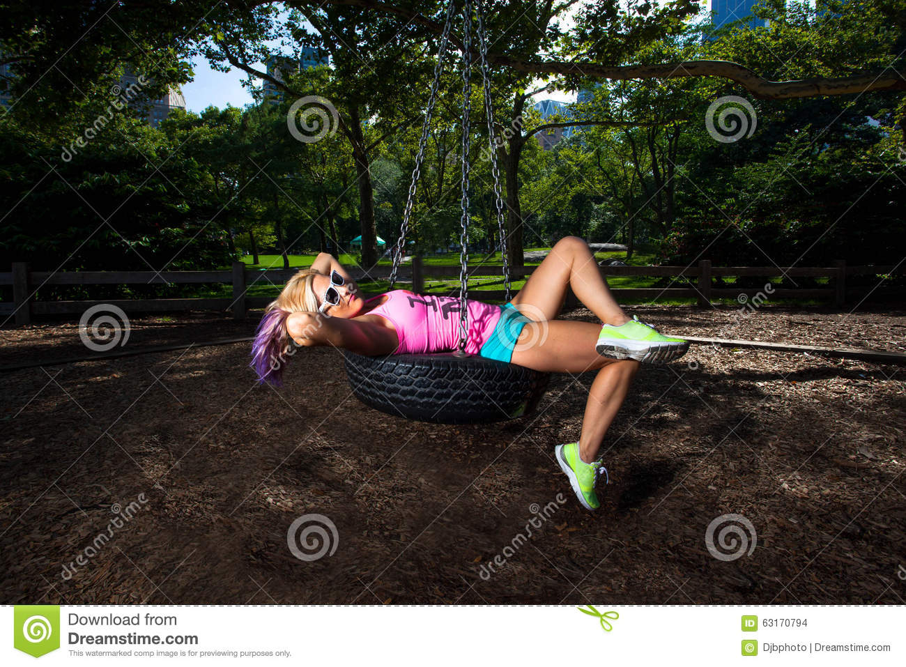 Young Blonde Athletic Woman Sitting On A Tire Swing Stock Photo ...