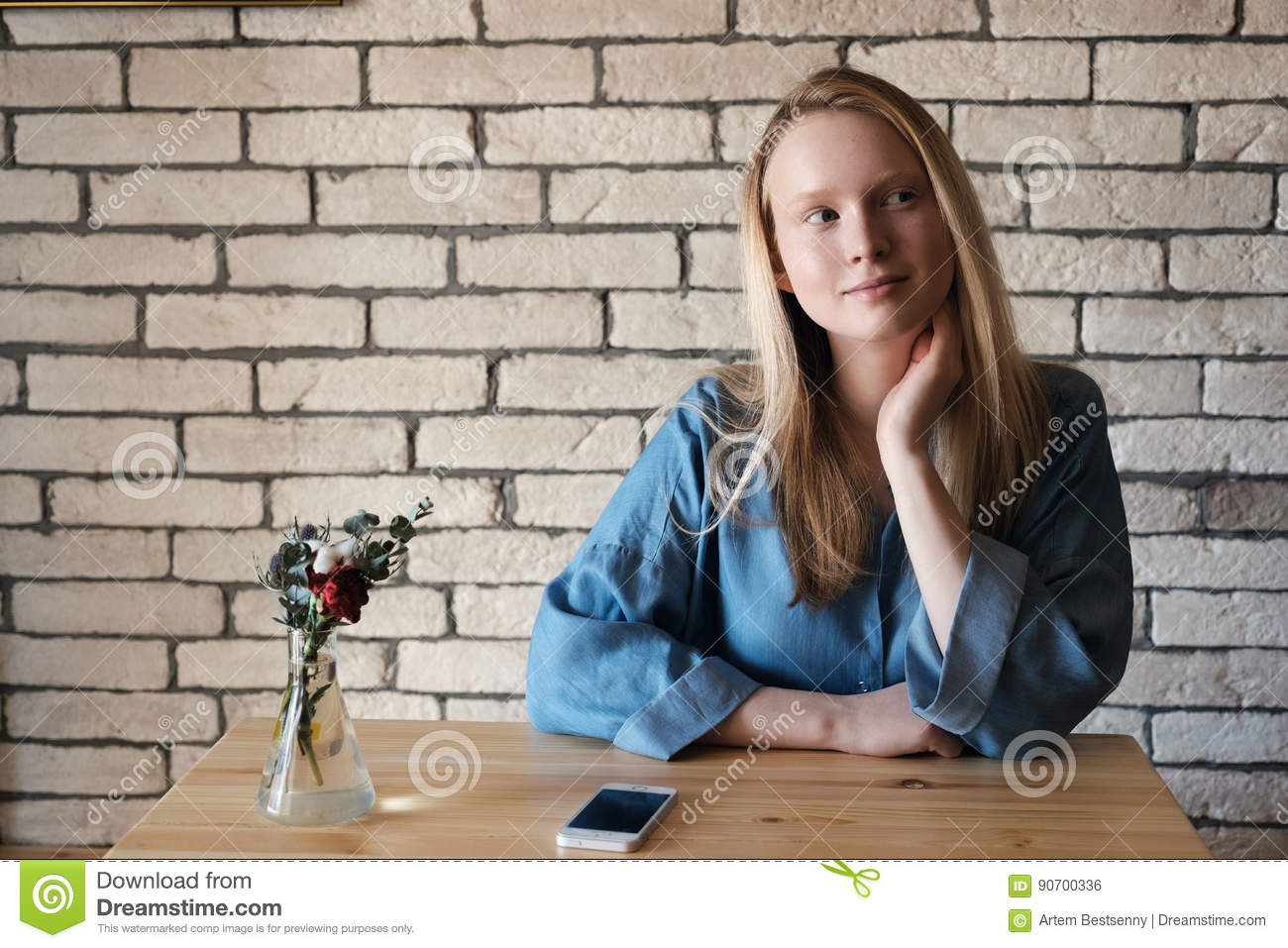 Young blonde in blue shirt sits at a table in a cafe on which lies a telephone