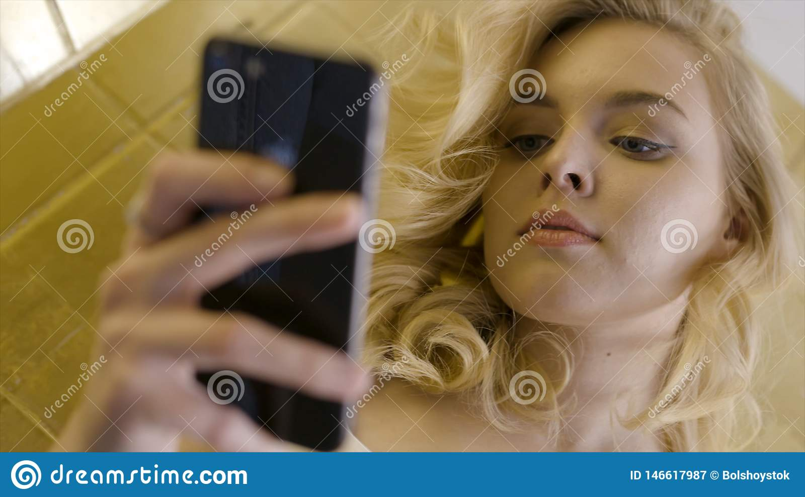 Young blonde chatting on phone. Action. Cheerful young blonde-haired female student with cute smile, using cell phone