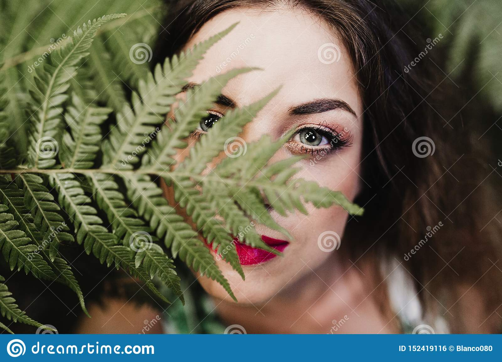 close up portrait of a young beautiful woman among green fern leaves looking at the camera. Beauty concept