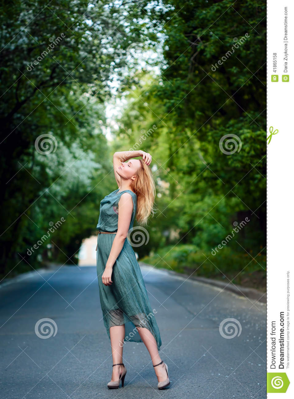 Young blonde girl dancing on the road